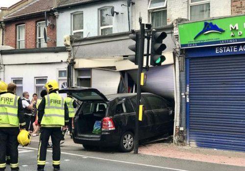 Driver flees after crashing car into shopfront and injuring a man